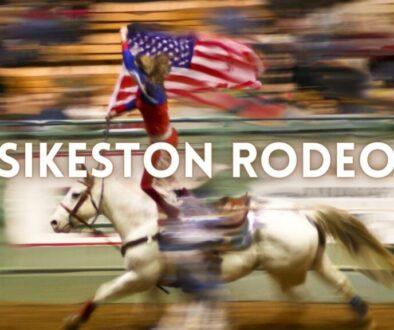 rodeo girl flying the American flag on horseback